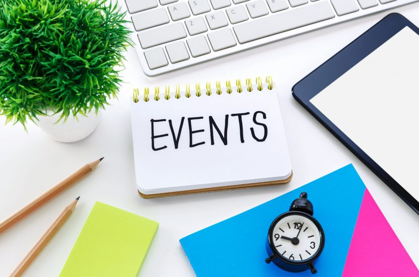 Notebook with events word on computer desk with pencil notepad and clock for event planning concept