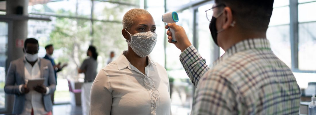 Receptionist measuring temperature of female employee at office's entrance - with face mask