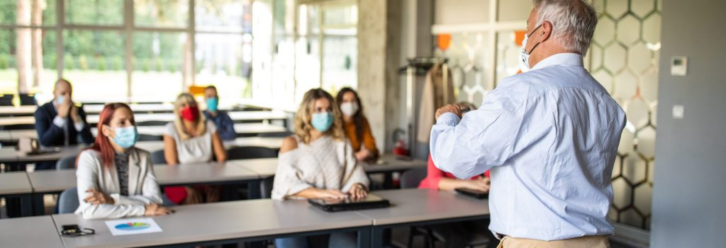 Presenter speaking in front of audience during education training class, they are wearing protective face masks for protection against virus during coronavirus pandemic